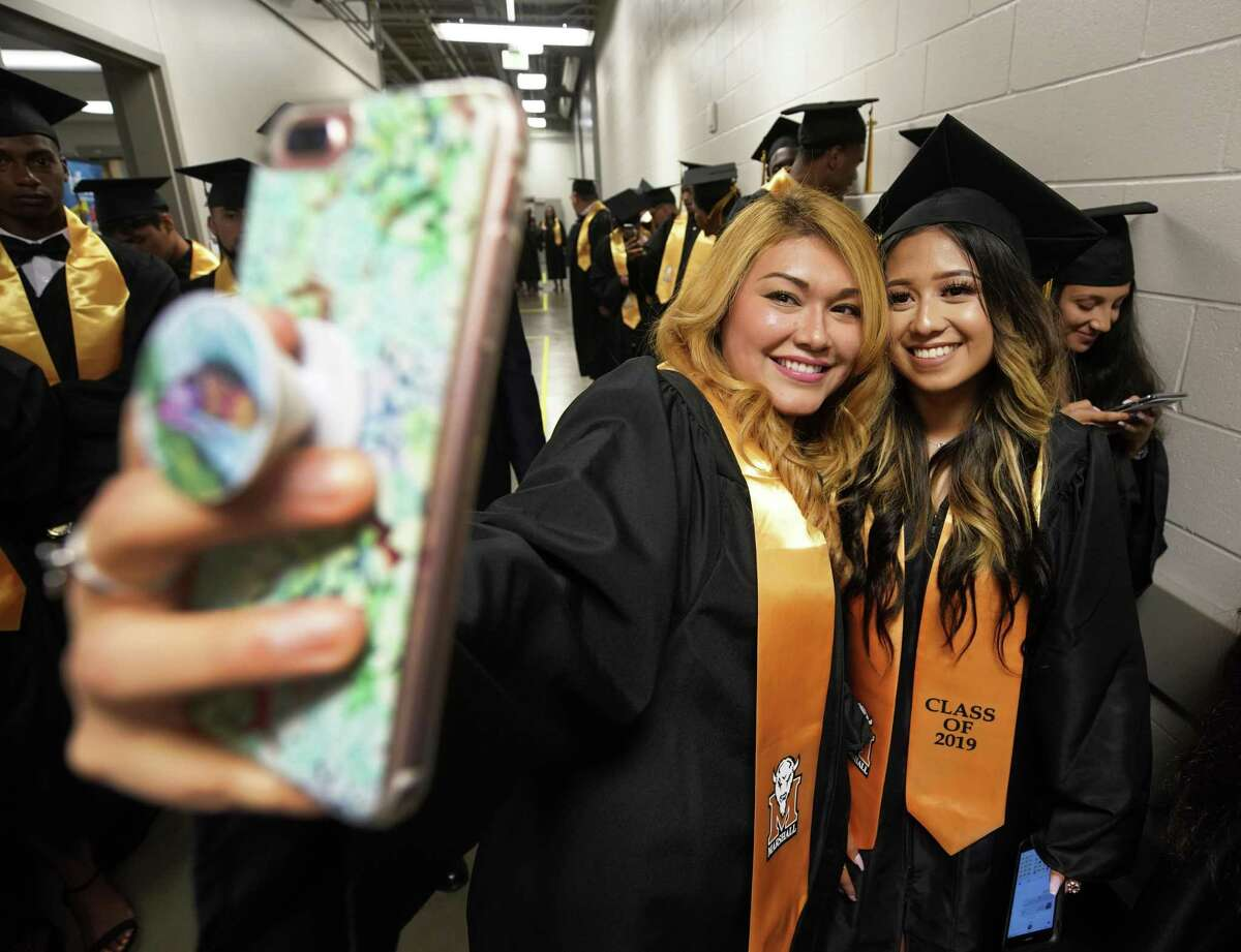 Thurgood Marshall High School teacher Bernice Rodriguez, left, takes a photo with Itzy Ramos, 18, as the students line up for graduation ceremony at Smart Financial Centre, 18111 Lexington Blvd., Saturday, May 25, 2019, in Sugar Land.