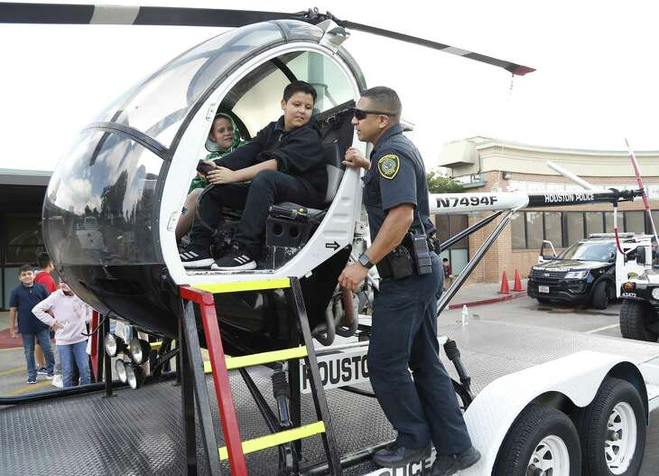 Senior Houston Police officer Gabriel Olvera shows Jorge Estrada, 11, the inside of a police helicopter during Career Day at MacArthur Elementary, a Gold Ribbon campus in Galena Park ISD, Thursday, May 23, 2019.