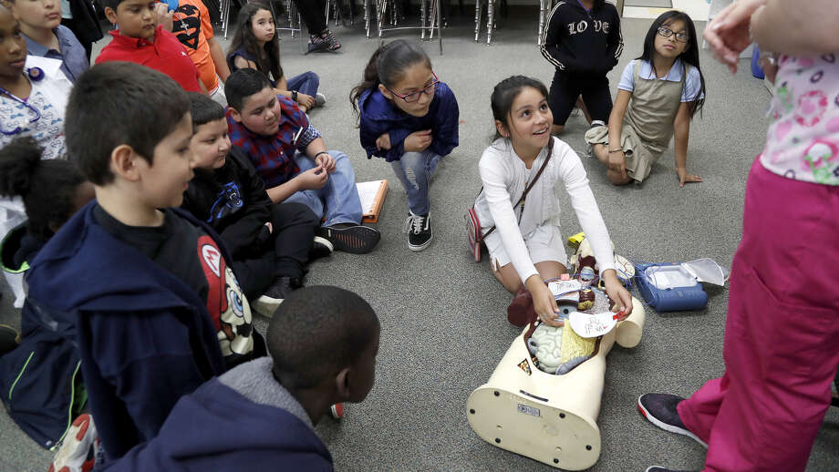"Angie Martinez, 9, looks up at Arial Hollow, a medical assistant, as she helped her demonstrate how to use a difibrilator during Career Day at MacArthur Elementary, a Gold Ribbon campus in Galena Park ISD, Thursday, May 23, 2019. Hollow is a former student at MacArthur Elementary and is part of the school's ""homegrown"" program. Photo: Karen Warren,  Houston Chronicle / Staff Photographer"