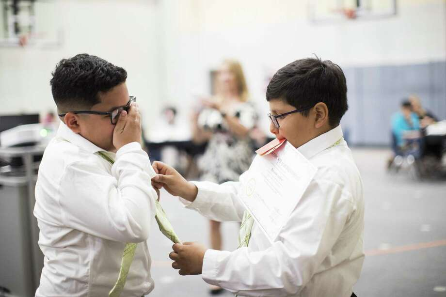 "Ricardo Ardon, right, helps Charles Cerda, left, with his new tie on Thursday, May 23, 2019, in Houston, during a ""Pearls For Girls"" and ""Ties For Guys"" event on Thursday, May 23, 2019, in Houston. The event was to celebrate the student members who completed the programs ""Pearls For Girls"" and ""Ties For Guys."" Photo: Marie D. De Jesús,  Houston Chronicle / Staff Photographer / © 2019 Houston Chronicle"