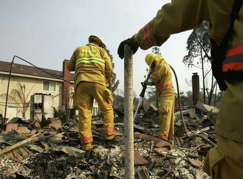 Firefighters douse a hot spot at a destroyed house in the Rancho Bernardo area of San Diego following the Witch Fire on Oct. 25, 2007. Photo: Chris Carlson / Associated Press / AP2007