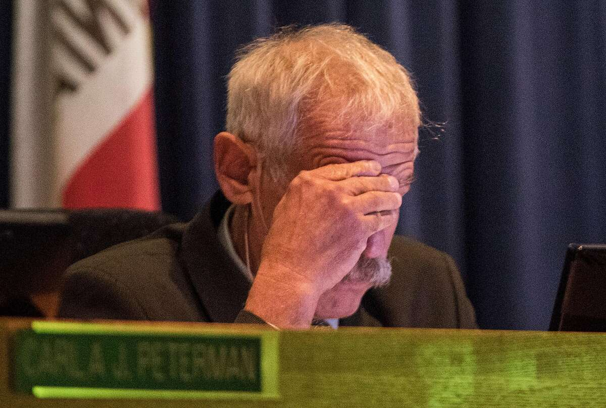 California Public Utilities Commission President Michael Picker rubs his forehead during the public comment portion of a California Public Utilities Commission meeting San Francisco, Calif. Wednesday, Nov. 28, 2018 surrounding the fate of PG&E following multiple deadly wildfires.