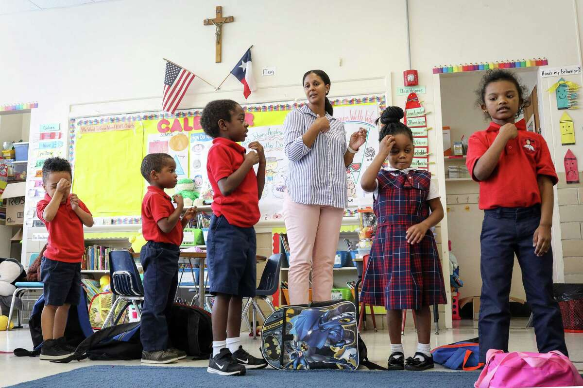 Julie Cook, pictured in May 2019, leads her students in making the sign of the cross after a prayer at the end of the school day at Saint Peter the Apostle Catholic School in Houston. The campus closed following that school year, and four other local private schools announced they will shutter this year amid the COVID-19 pandemic.