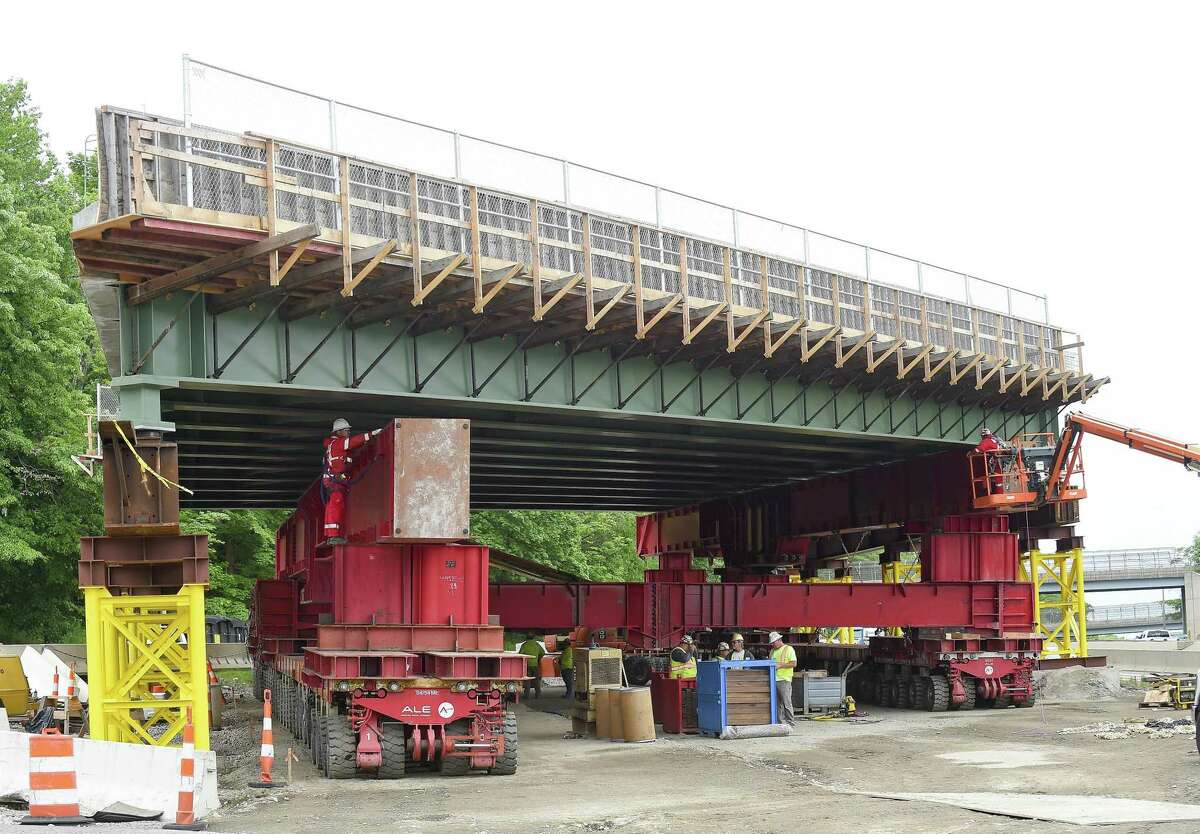 Workers prepare a Self Propel Modular Transport (SPMT) system under one of two separate spans of prefabricated bridge on May 29, 2019, that will be installed as part of the bridge replacement project at Exit 9 in Stamford, Connecticut. Using accelerated bridge construction technology, the spans will be rolled into place over two weekends.