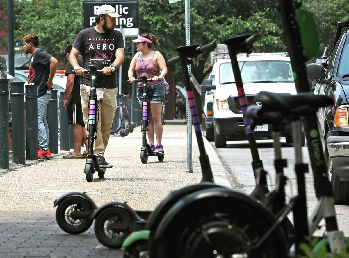 Jose Velasquez, left, and Joanna Escobedo, here in San Antonio from the Valley on vacation, ride scooters on the side walk on Presa Street. The City Council voted to ban riding scooters on sidewalks by June 30.