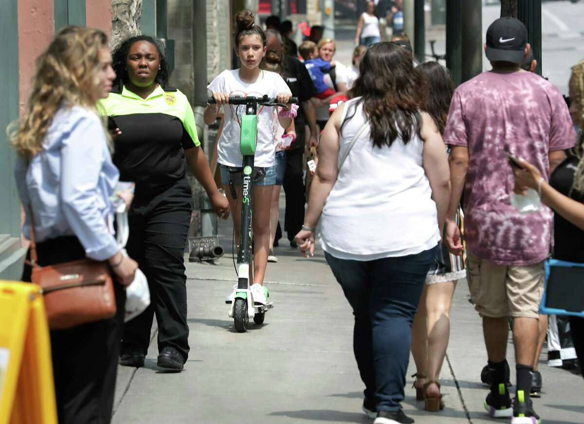 A young girl rides a scooter on a crowded side walk on Commerce Street on Thursday, May, 30, 2019. The City Council voted to ban riding scooters on sidewalks by June 30.