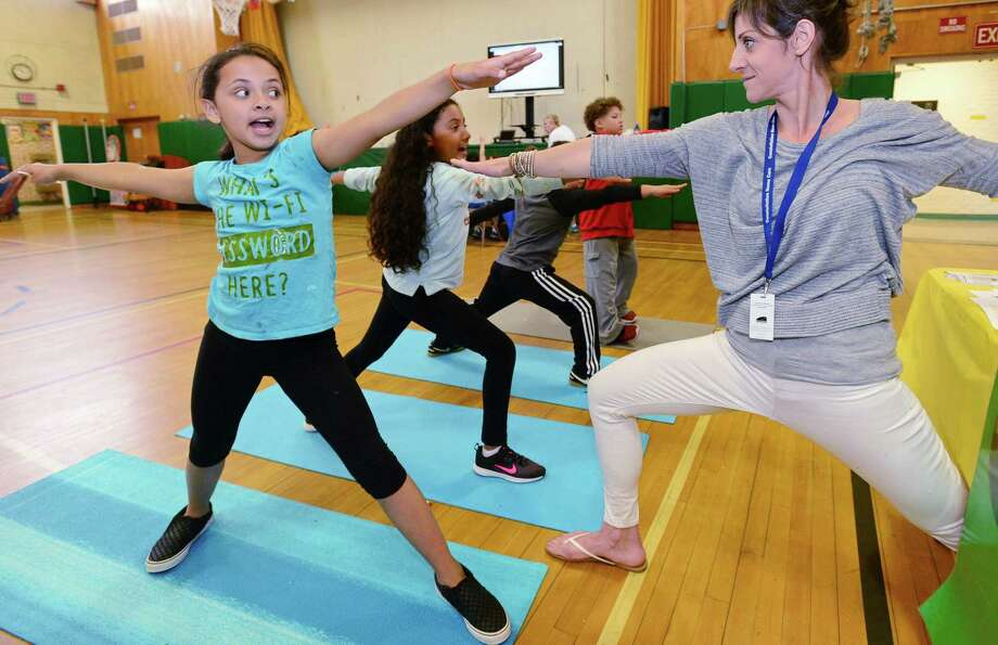 """School Physical Therapist Eleni Kaufman, right, teaches 4th grader Kassidey Langrin and her classmates the Warrior pose at the Yoga Station during Fox Run Elementary School's """"Celebrating Differences Day,"""" Thursday, May 30, 2019 , in Norwalk, Conn. The event seeks to promote awareness of disabilities like hearing impairments, learning disabilities, autism and fine or gross motor disabilities. Students participated in simulations that are meant to demonstrate the experience of living with a disability. Photo: Erik Trautmann / Hearst Connecticut Media / Norwalk Hour"""