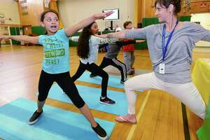 "School Physical Therapist Eleni Kaufman, right, teaches 4th grader Kassidey Langrin and her classmates the Warrior pose at the Yoga Station during Fox Run Elementary School's ""Celebrating Differences Day,"" Thursday, May 30, 2019 , in Norwalk, Conn. The event seeks to promote awareness of disabilities like hearing impairments, learning disabilities, autism and fine or gross motor disabilities. Students participated in simulations that are meant to demonstrate the experience of living with a disability."