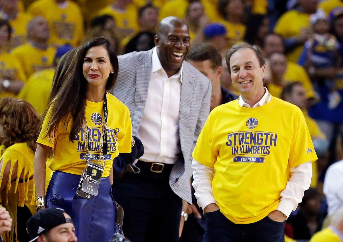 Golden State Warriors owner Joe Lacob, right, smiles next to his fiance Nicole Curran, left, and former basketball player Magic Johnson during the first half of Game 1 of basketball's NBA Finals between the Warriors and the Cleveland Cavaliers in Oakland, Calif., Thursday, June 4, 2015. (AP Photo/Ben Margot)