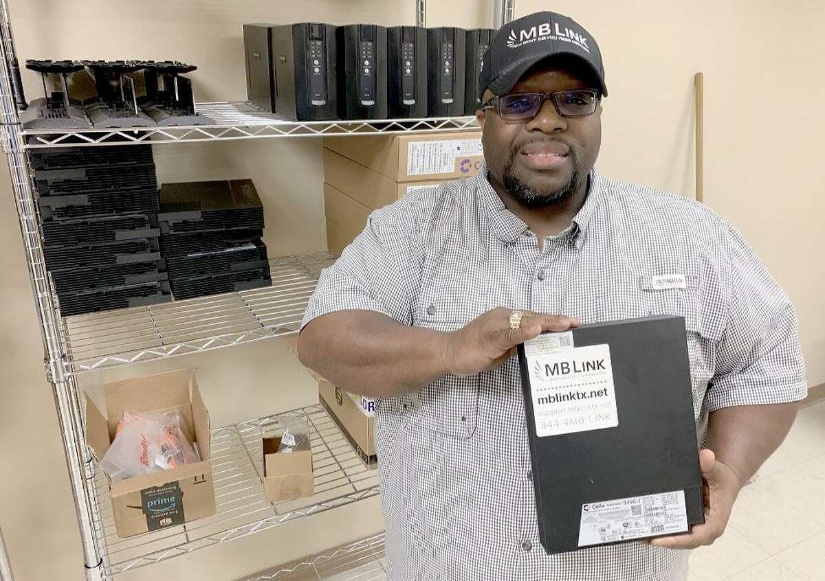 Dwight Thomas, Mont Belvieu's director of broadband and IT systems, holds one of the fiber optic modems that are placed in MB Link customers' homes.