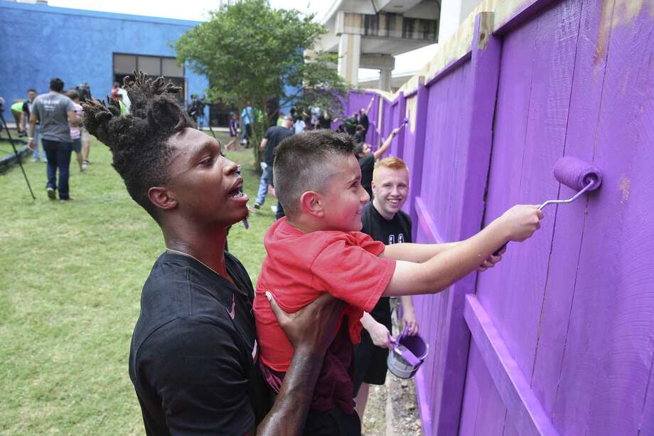Spurs' Lonnie Walker, IV (left) gives nine-year-old Mario Barrera a lift to paint the upper sections of fencing as Spurs players and staff pay a visit to SA Youth to help them paint and refurbish the playscape and fence line on the nonprofit's 1215 W. Poplar Street campus to help promote a healthy and active lifestyle on Thursday, May 30, 2019. Last year, Silver and Black Give Back donated a new basketball court for the more than 1,500 children served by SA Youth through Operation Renovation. Walker joined by teammates Drew Eubanks, Chimezie Metu and Ben Moore as they were all-hands-on-deck when joining kids and volunteers from SA Youth and Spurs Sports & Entertainment to put the finishing touches on the refurbished playground and help provide a safer space to learn, grow, and play. (Kin Man Hui/San Antonio Express-News) Photo: Kin Man Hui, Staff / Staff Photographer / ©2019 San Antonio Express-News
