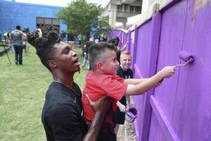 Spurs' Lonnie Walker, IV (left) gives nine-year-old Mario Barrera a lift to paint the upper sections of fencing as Spurs players and staff pay a visit to SA Youth to help them paint and refurbish the playscape and fence line on the nonprofit's 1215 W. Poplar Street campus to help promote a healthy and active lifestyle on Thursday, May 30, 2019. Last year, Silver and Black Give Back donated a new basketball court for the more than 1,500 children served by SA Youth through Operation Renovation. Walker joined by teammates Drew Eubanks, Chimezie Metu and Ben Moore as they were all-hands-on-deck when joining kids and volunteers from SA Youth and Spurs Sports & Entertainment to put the finishing touches on the refurbished playground and help provide a safer space to learn, grow, and play. (Kin Man Hui/San Antonio Express-News)