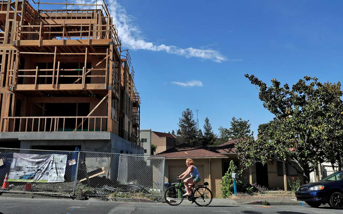 A cyclist rides by new, luxury condo construction next to a single-family home on Trinity Avenue in Walnut Creek, Calif., on Sunday, May 5, 2019. State Sen. Scott Wiener's SB50, besides allowing denser housing near transit, would wipe out single-family zoning in many suburban cities and allow apartment construction in such areas.