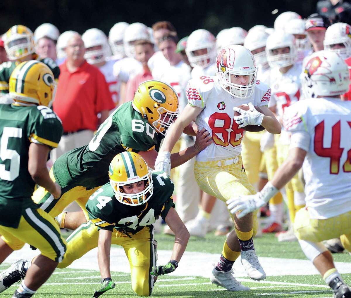 Trinity Catholic High School defender Evan Field (#34), bottom, faces an uncertain sports future as several programs have been cut due to dwindling enrollment, including football.