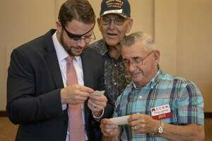 U.S. Rep. Dan Crenshaw TX-2  looks at old World War II photos with veteran Jerry Wilkinson and his friend Charles Calloway at the Odessa Country Club.  Jacy Lewis/191 News