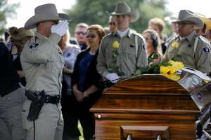 Members of the Midland County Sheriff's Office Honor Guard place roses on the casket and salute during the funeral for Midland County Sheriff Gary Painter May 30, 2019 at Resthaven Memorial Park.  James Durbin/Reporter-Telegram