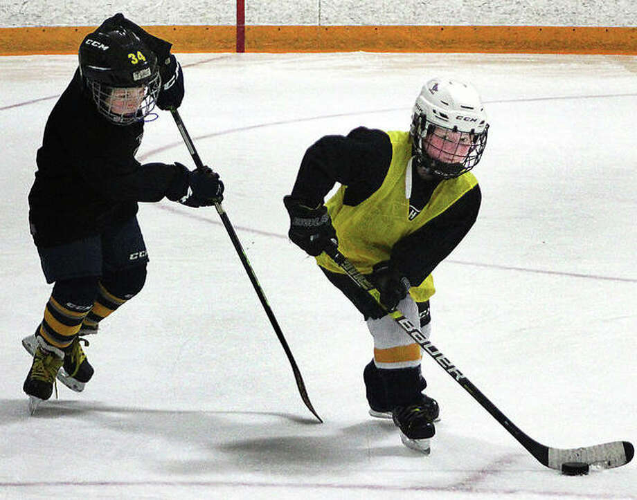 A pair of young skaters scrimmage Thursday evening at the East Alton Ice Arena. The session was conducted by the Elite Hockey Facility of East Alton. Photo: Pete Hayes | The Telegraph
