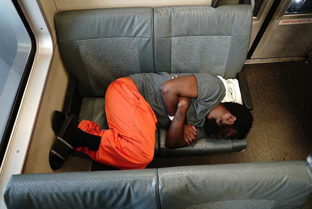 Rolontei Simril, 28, who has been homeless for 8-years, uses a rag for a pillow as he sleeps on the SFO/Antioch BART train on Thursday, May 30, 2019, in San Francisco, CA.