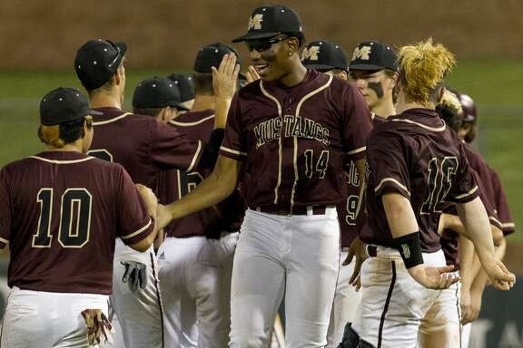 Magnolia West's Seth Hayes, center, gives Willis Ibarra a high-five after the team's 2-1 win over Georgetown in Game 1 of a Region III-5A final series at Blue Bell Park on the campus of Texas A&M University, Thursday, May 30, 2019, in College Station.
