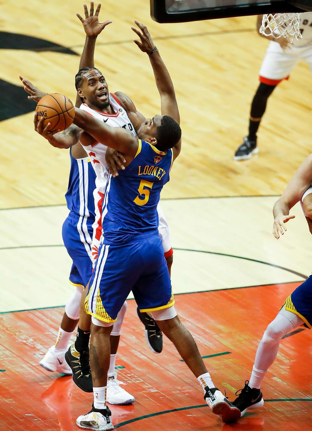 Golden State Warriors' Draymond Green and Kevon Looney defend against Toronto Raptors' Kawhi Leonard in the second quarter during game 1 of the NBA Finals between the Golden State Warriors and the Toronto Raptors at Scotiabank Arena on Thursday, May 30, 2019 in Toronto, Ontario, Canada.