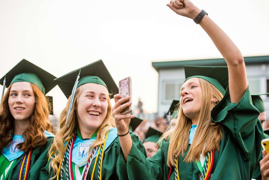 Graduate Taylor Bakos, right, cheers on a friend as Madison Wegner, left, laughs at the Freeland High School Commencement Ceremony on Thursday. (Danielle McGrew Tenbusch/for the Daily News) Photo: (Danielle McGrew Tenbusch/for The Daily News)
