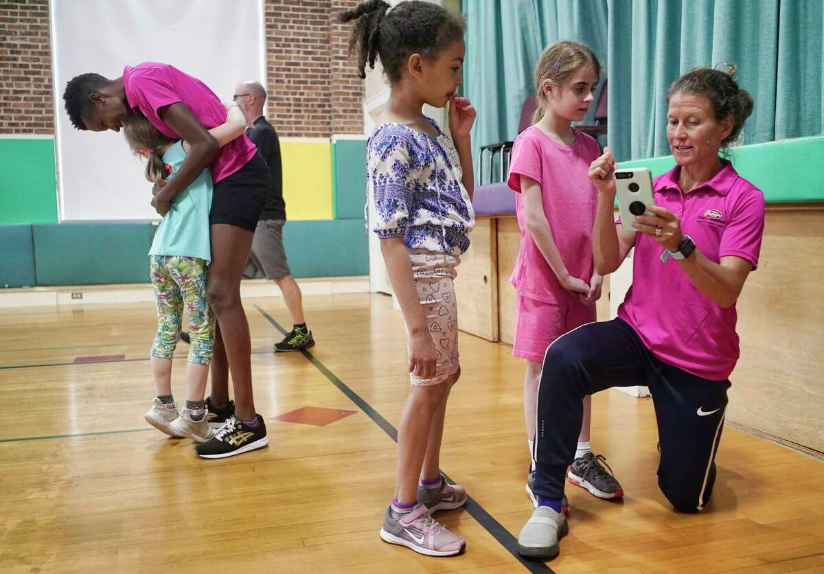 Runner Diane Nukuri, left, gets a hug from a student as runner Melody Fairchild shows children how to sign up for the Freihofer's children's race, as the two women paid a visit to Elsmere Elementary School on Thursday, May 30, 2019, in Delmar, N.Y. The two runners will compete in the Freihofer's Run for Women race on Saturday. (Paul Buckowski/Times Union)