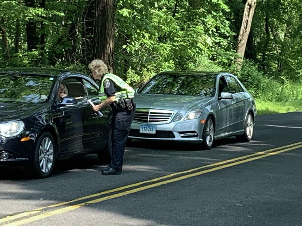New Canaan Police Lt. Carol Ogrinc hands out missing persons flyers of Jennifer Dulos on Friday on Lapham Road near where the woman's SUV was found last week.