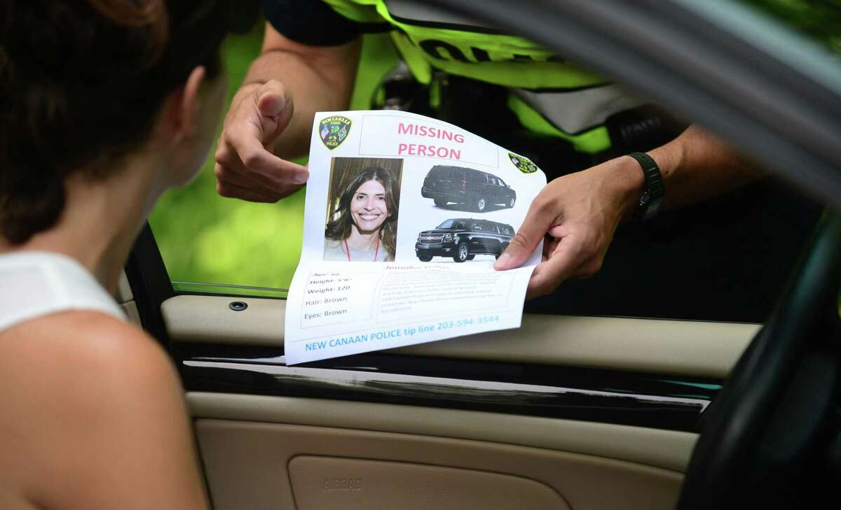 New Canaan police hand out missing persons flyers on Friday in hopes of finding Jennifer Dulos near where her SUV was found on Lapham Road.