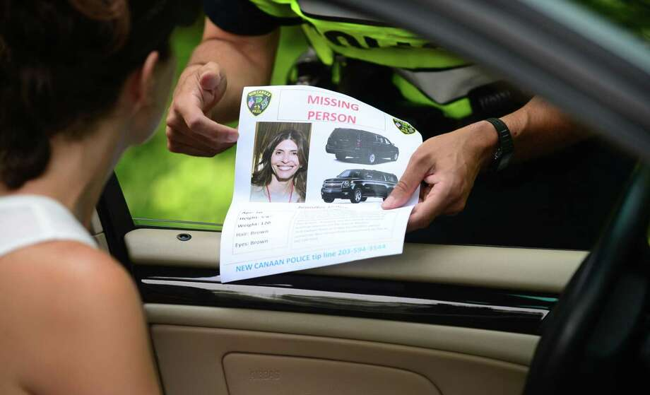New Canaan police hand out missing persons flyers on Friday in hopes of finding Jennifer Dulos near where her SUV was found on Lapham Road. Photo: Erik Trautmann / Hearst Connecticut Media