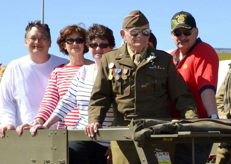 Surrounded by his family, Technical Sergeant John Trippon serves as grand marshal of the parade at the 70th anniversary of D-Day in Normandy, France, in 2014. Photo: Courtesy Photo