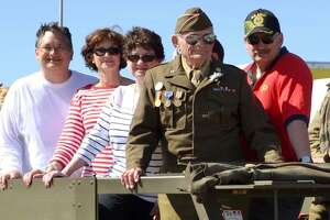 Surrounded by his family, Technical Sergeant John Trippon serves as grand marshal of the parade at the 70th anniversary of D-Day in Normandy, France, in 2014.