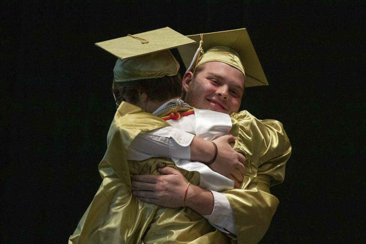 Conroe salutatorian Kyle Mrosko hugs valedictorian Preston Hart as Hart prepares to walk the stage during a graduation ceremony Wednesday, May 29, 2019 at The Cynthia Woods Mitchell Pavilion in The Woodlands.