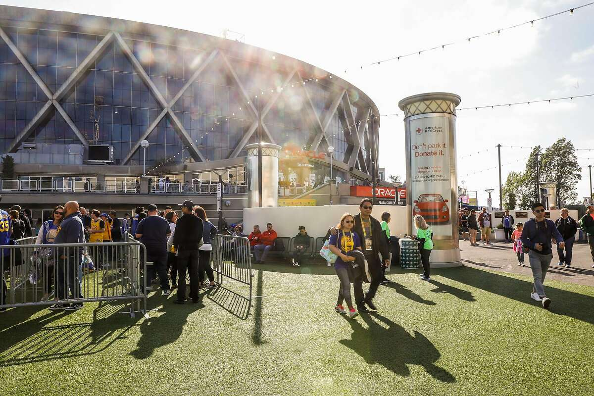 Fans walk outside Oracle Arena ahead of Game 5 of the Western Conference Semifinals between the Golden State Warriors and the Houston Rockets at Oracle Arena in Oakland, California, on Wednesday, May 8, 2019. The series is tied 2-2.