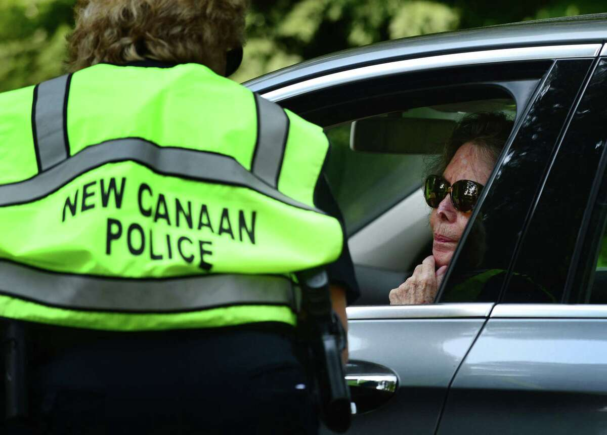 New Canaan police ask motorists and pedestrians about a missing New Canaan woman Friday at Waveny Park in New Canaan, Conn.