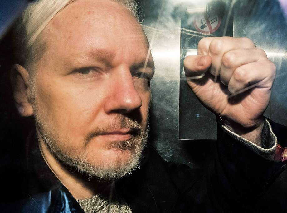 "(FILES) In this file photo taken on May 01, 2019 WikiLeaks founder Julian Assange gestures from the window of a prison van as he is driven out of Southwark Crown Court in London, after having been sentenced to 50 weeks in prison for breaching his bail conditions in 2012. - Julian Assange has been subjected to drawn-out ""psychological torture"", a UN rights expert said May 31, 2019, accusing the United States, Britain, Ecuador and Sweden of ""collective persecution"" of the WikiLeaks founder. The United Nations special rapporteur on torture and other cruel, inhuman or degrading treatment, Nils Melzer, also warned that if London agrees to an extradition request from Washington, Assange risked the death penalty. (Photo by Daniel LEAL-OLIVAS / AFP)DANIEL LEAL-OLIVAS/AFP/Getty Images Photo: Daniel Leal-olivas, AFP/Getty Images"
