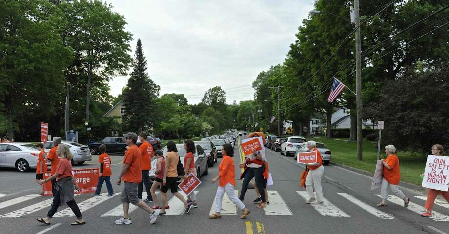 Activists from Newtown and across Connecticut wore orange and walked to raise awareness of gun violence during the second annual national Gun Violence Awareness Day. Thursday, June 2, 2016, in Newtown, Conn. Walkers cross Main Street on their way to Edmund Town Hall. Photo: H John Voorhees III / Hearst Connecticut Media / The News-Times