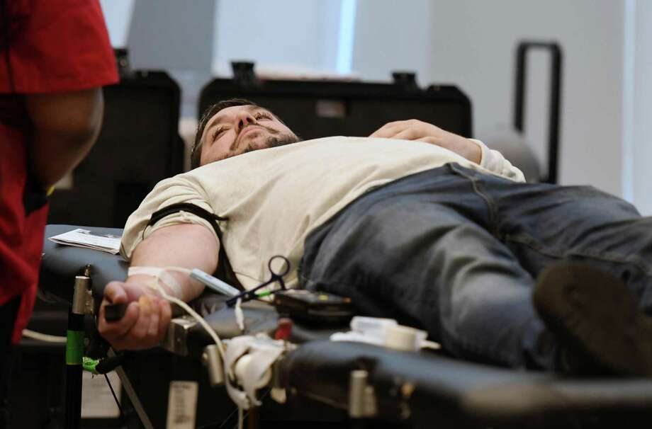 Matthew Peter gives blood during a blood drive in memory of Detective Jason Martin on Friday, April 26, 2019 at the Albany Capital Center in Albany, NY. Detective Jason Martin was a lifelong resident of Albany who worked for the city for 20 years and died last year of lung cancer. (Phoebe Sheehan/Times Union) Photo: Phoebe Sheehan, Staff Photographer / Albany Times Union / 20046666A