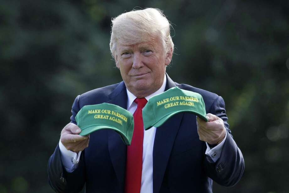"President Trump holds hats with the message ""Make Our Farmers Great Again"" at the White House in Washington, Aug. 30. A reader argues Trump's $15 billion pay-back to farmers is socialistic. Photo: TOM BRENNER /NYT / NYTNS"