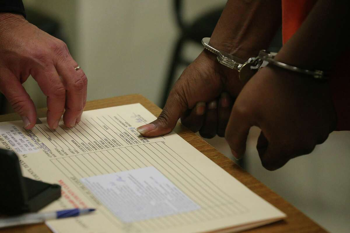 A defendant is fingerprinted in jail court, also known as Auxiliary Court, at the Bexar County Jail.