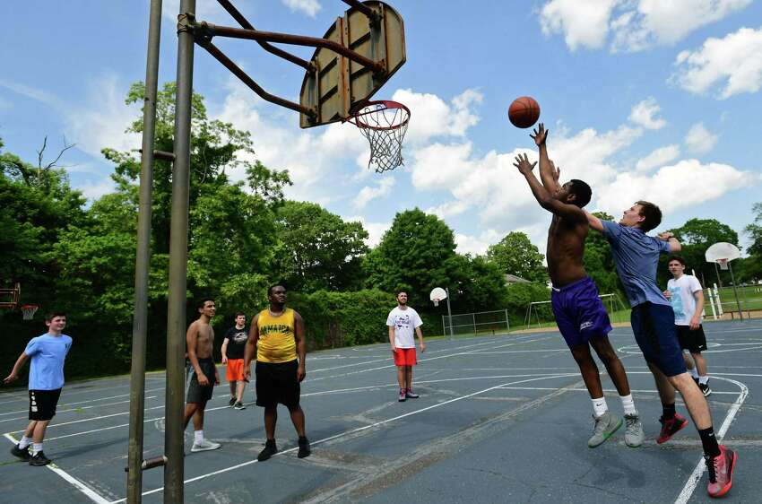 A group of friends plays pick up basketball at Fitch Playground Friday, May 31, 2019, in Norwalk, Conn.