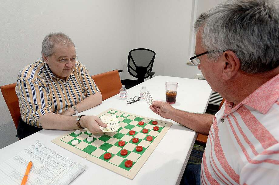 World Champion Alex Moiseyev (left) watches as Texas State Champion Watson Franks of Vidor draws the card determining the opening move during the American Checkers Federation District 8 and Texas State Championship Checkers Tournament, which started Friday at the Holiday Inn in Vidor. The finals and award ceremony is being held Saturday. Photo taken Friday, May 31, 2019 Kim Brent/The Enterprise Photo: Kim Brent / The Enterprise / BEN
