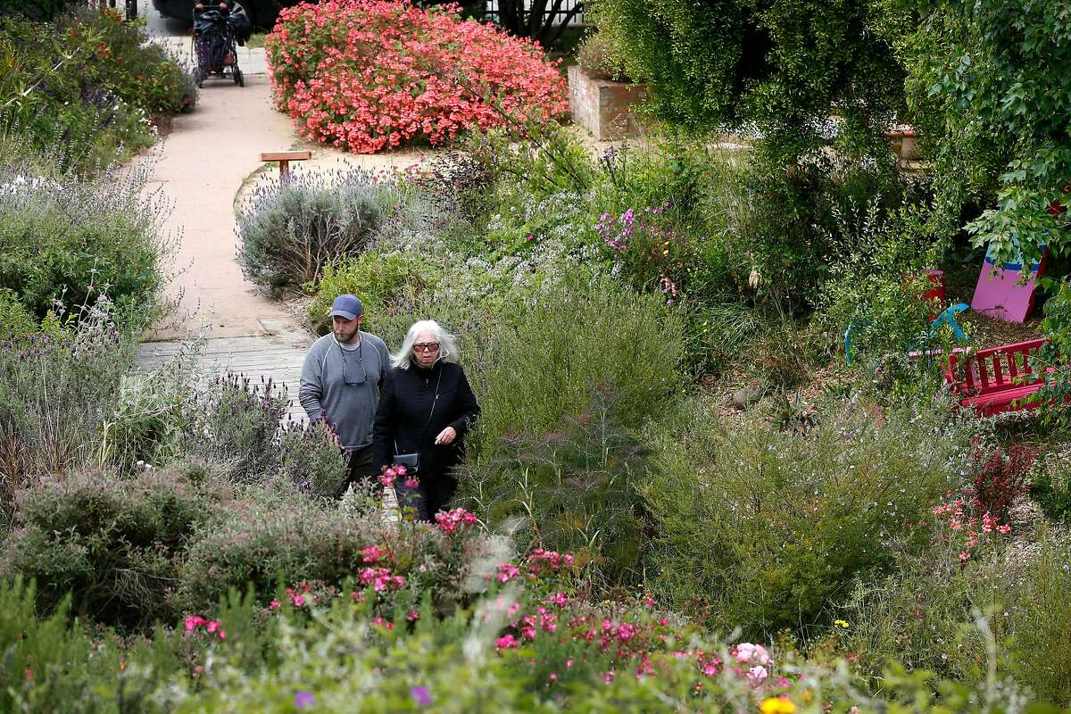 Fran Martin (right), co-founder of the Visitacion Valley Greenway, walks on the path with Brian Perrin, curator of a sculpture exhibit located in the herb garden section of the park in San Francisco, Calif. on Thursday, May 30, 2019.