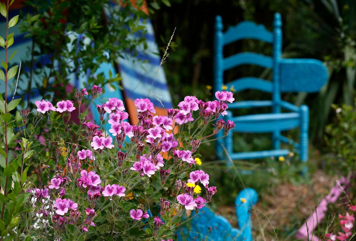 Flowers bloom in front of a sculpture by artist Sofie Ramos that is on display in the herb garden area of the Visitacion Valley Greenway in San Francisco, Calif. on Thursday, May 30, 2019.