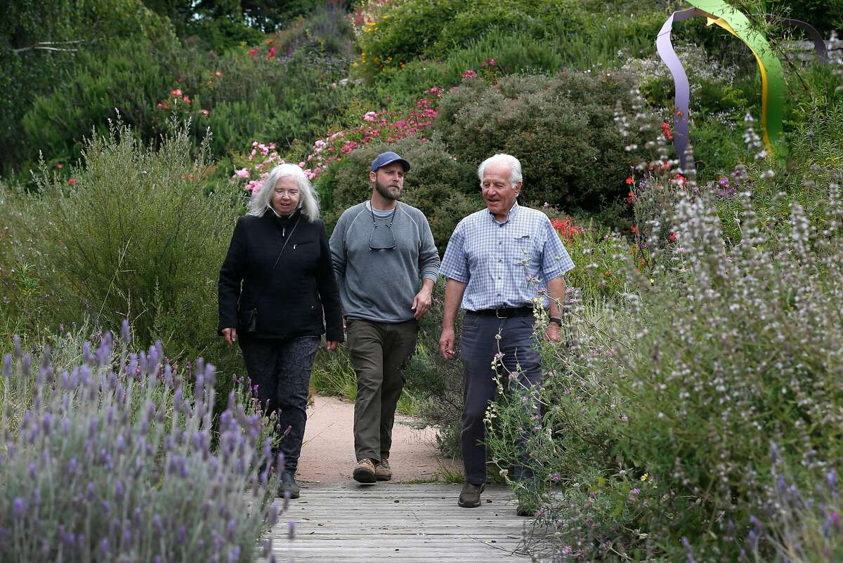 Fran Martin (left), co-founder of the Visitacion Valley Greenway, walks on the path with Brian Perrin (center), curator of a sculpture exhibit located in the herb garden section of the park, and Bob Siegel in San Francisco, Calif. on Thursday, May 30, 2019.