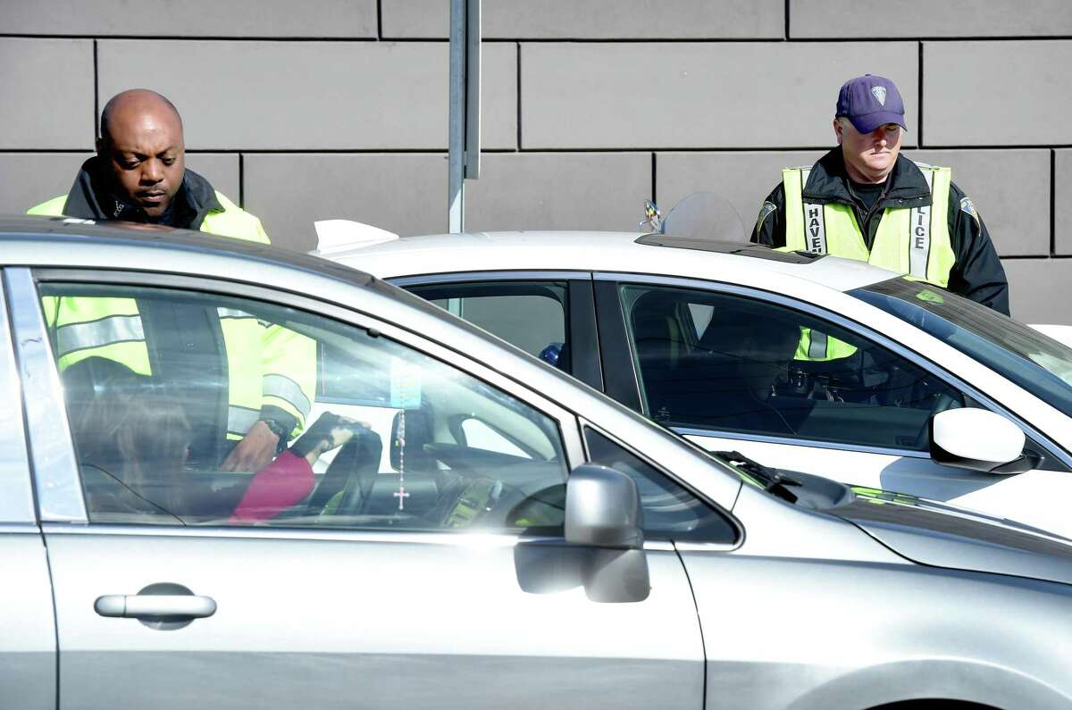 New Haven Police Officers Quintarus McArthur (left) and Scott Durkin (right) speaks with drivers pulled over for distracted driving on North Frontage Roa. in New Haven on April 12, 2016.