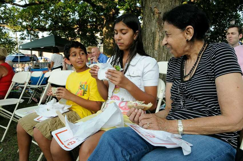 Sofie Merchant, Stamford, enjoys a picnic with her grandchildren Noor Merchant, 11, and Omar Merchant, 10, Stamford. Several hundred people gathered in Columbus Park in Stamford on Wednesday evening, July 28, 2010 for the Pops in the Park concert, featuring Bowser's Rock 'n' Roll Party, along with an assembly of more than 50 antique cars, most from the fifties and sixties.