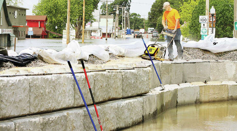 A worker Friday compacts the rock on top of Grafton's first-ever block flood wall across Main Street to keep floodwaters from their Village Hall and businesses to the east of N. Vine Street. The wall uses large concrete blocks similar to those used in the Alton flood wall. In previous floods only sandbagging was used and that proved ineffective during the Great Flood of 1993. The village has also added rock and fortified the flood route through town on West Washington Street. Sandbaggers on the Village Hall parking lot were seeking volunteers Friday afternoon. Photo: John Badman | The Telegraph