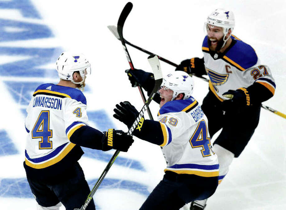 The Blues' Carl Gunnarsson (4) is congratulated by Ivan Barbashev (49) and Alex Pietrangelo, right, after he scored the winning goal in overtime Wednesday iun game 2 of the Stanley Cup Finals against the Boston Bruins at TD Garden. Photo: AP Photo