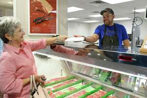 Butcher Miguel Morales, right, assists customer Sandy Schmidt at Midway Meat Market in Katy on Wednesday, May 29.