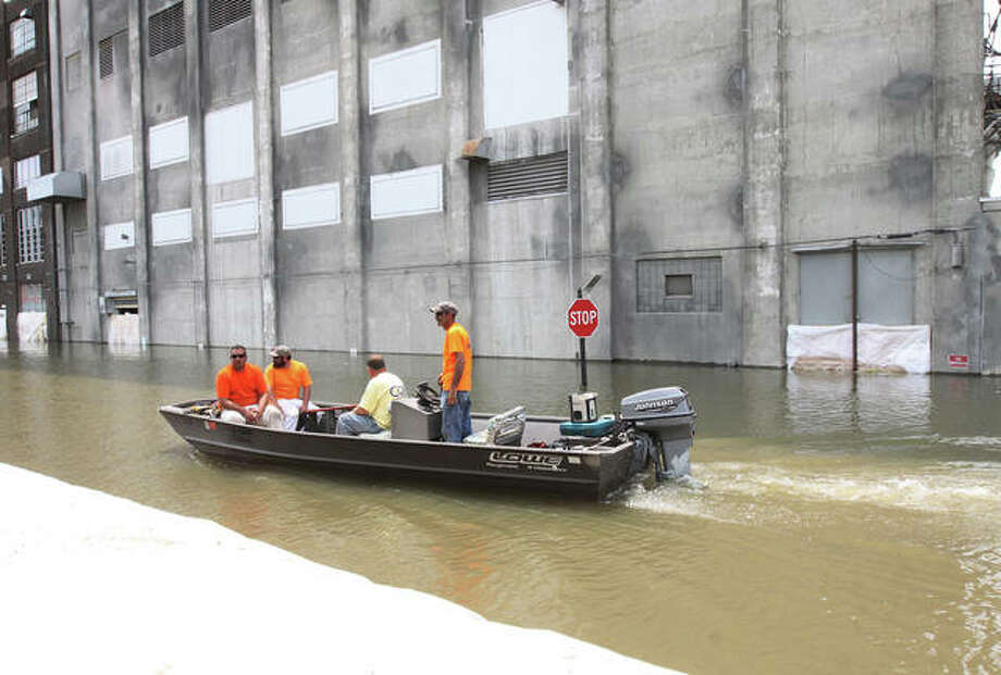 Alton City workers boat down West Broadway Friday to help drop sandbags on the river side of the floodwall. Photo: John Badman | The Telegraph